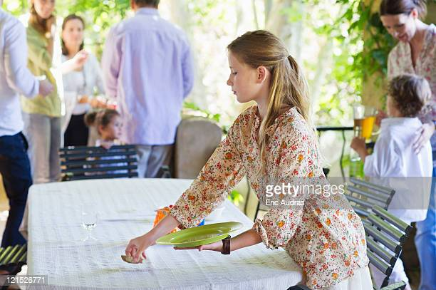 little girl cleaning dining table after eating food with family in the background - cleaning after party stock pictures, royalty-free photos & images