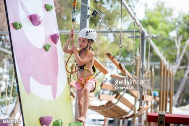 Kleines Mädchen Klettern im Abenteuerpark