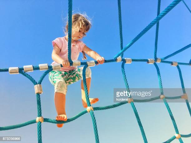 Little girl climbing rope ladder on the playground