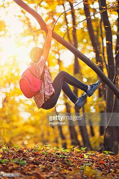 Kleines Mädchen klettert am Baum im Herbst
