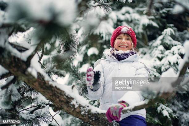 Little girl climbing tree in the snow forest