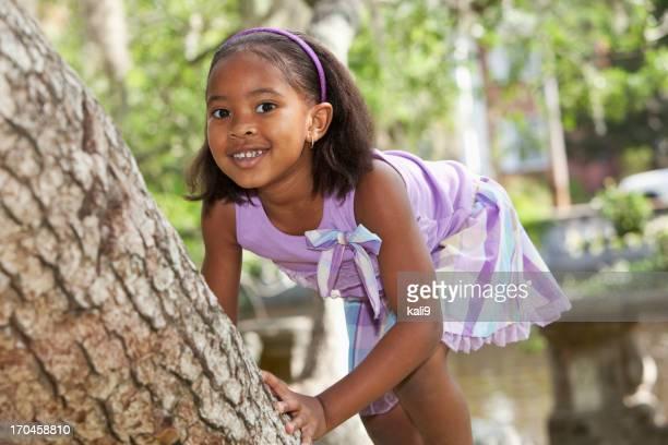 Little girl climbing árbol