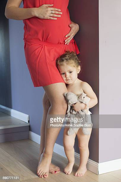 little girl clinging to her pregnant mothers leg with worried expression on face - anne sophie mutter stock-fotos und bilder
