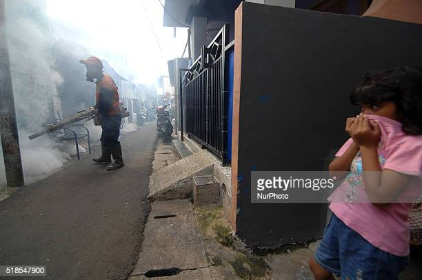 A little girl closes face as health clerks perform fumigation against Aedes aegypti mosquitoes that transmit dengue in densely populated settlements...