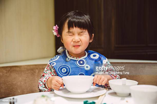 Little girl closing her eyes in restaurant