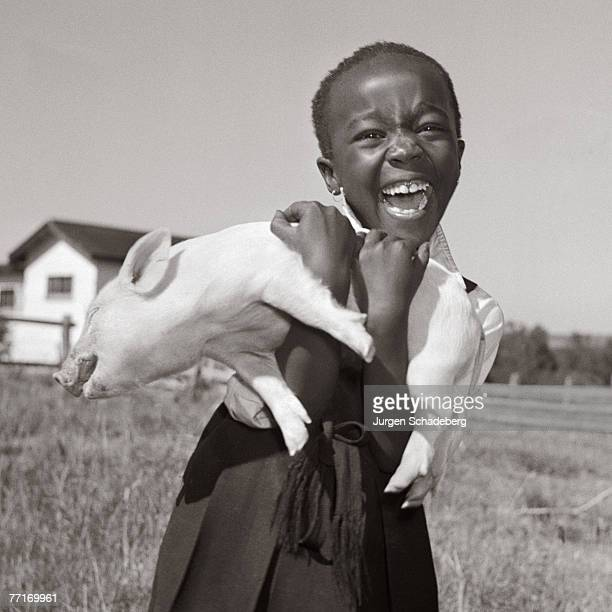 A little girl clutches a piglet to her chest during a visit to a farm in Muldersdrift Gauteng Province South Africa 1952