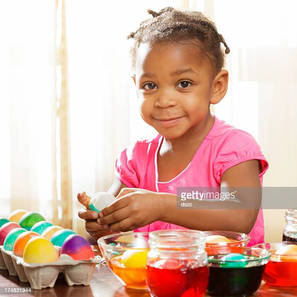 little girl coloring easter eggs - african-american child - african american easter stock photos and pictures