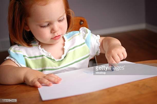Little Girl Coloring in a School Desk