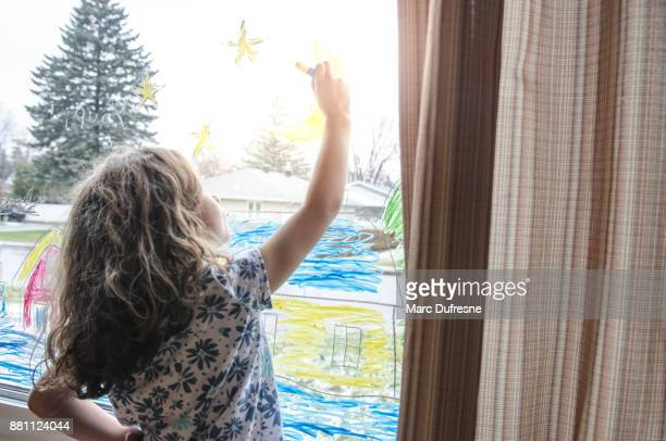 Petite fille à colorier sur la fenêtre du salon une ambiance d'hiver pour être vu de l'extérieur