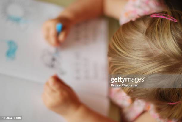 little girl coloring with a color pencil in a coloring book - kristina strasunske stock pictures, royalty-free photos & images
