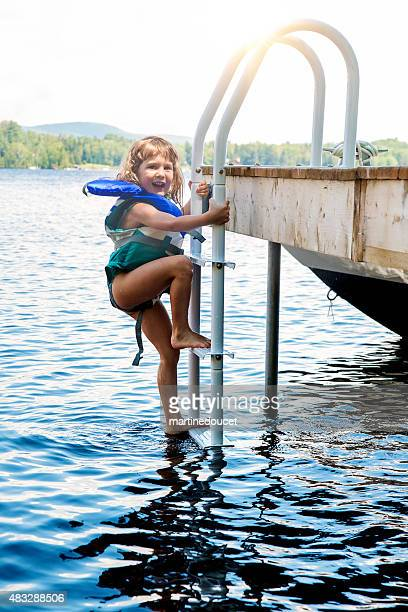 """little girl coming out of lake climbing on pier ladder. - """"martine doucet"""" or martinedoucet stockfoto's en -beelden"""