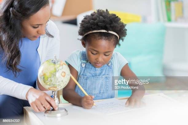 Little girl completes assignment on globes