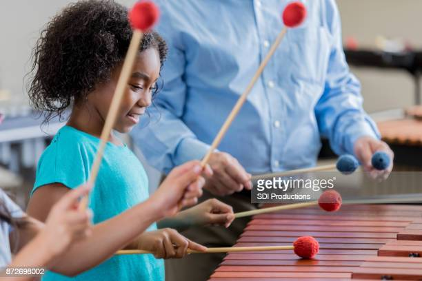 little girl concentrates during xylophone practice - train band stock photos and pictures