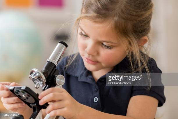 Little girl concentrates while using microscope