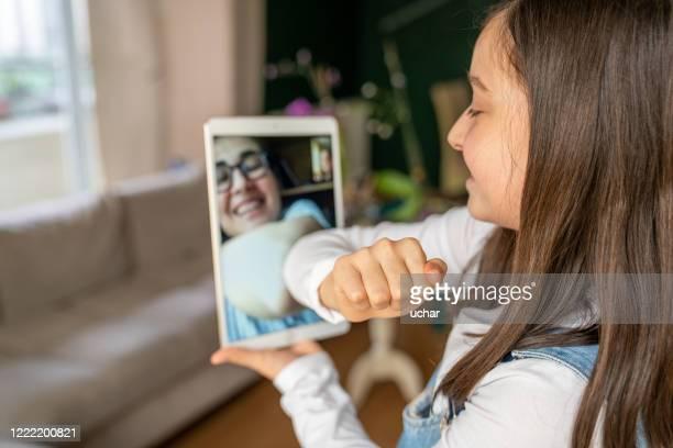 petite fille félicite avec tablette numérique en raison de covid-19 - éviter de se serrer la main photos et images de collection