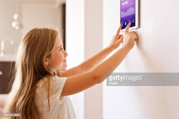 little girl controlling smart devices with a digital tablet at home - smart stock pictures, royalty-free photos & images