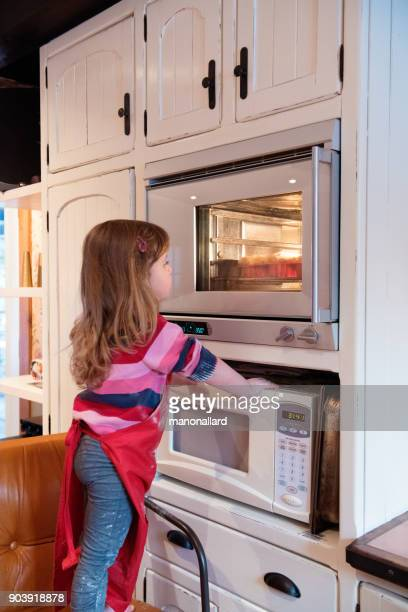 Little girl cooking cookies during Valentine's Day
