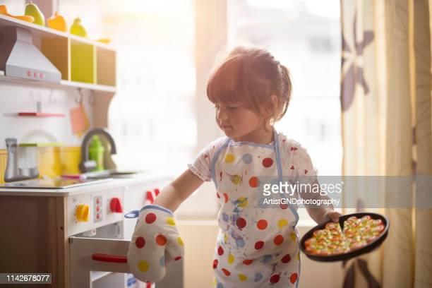 klein meisje koken op decoratieve keuken thuis. - 2 3 jaar stockfoto's en -beelden