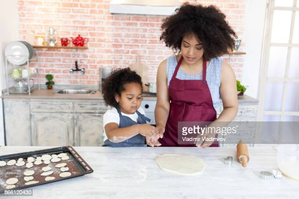 Little girl cooking with her mother at home