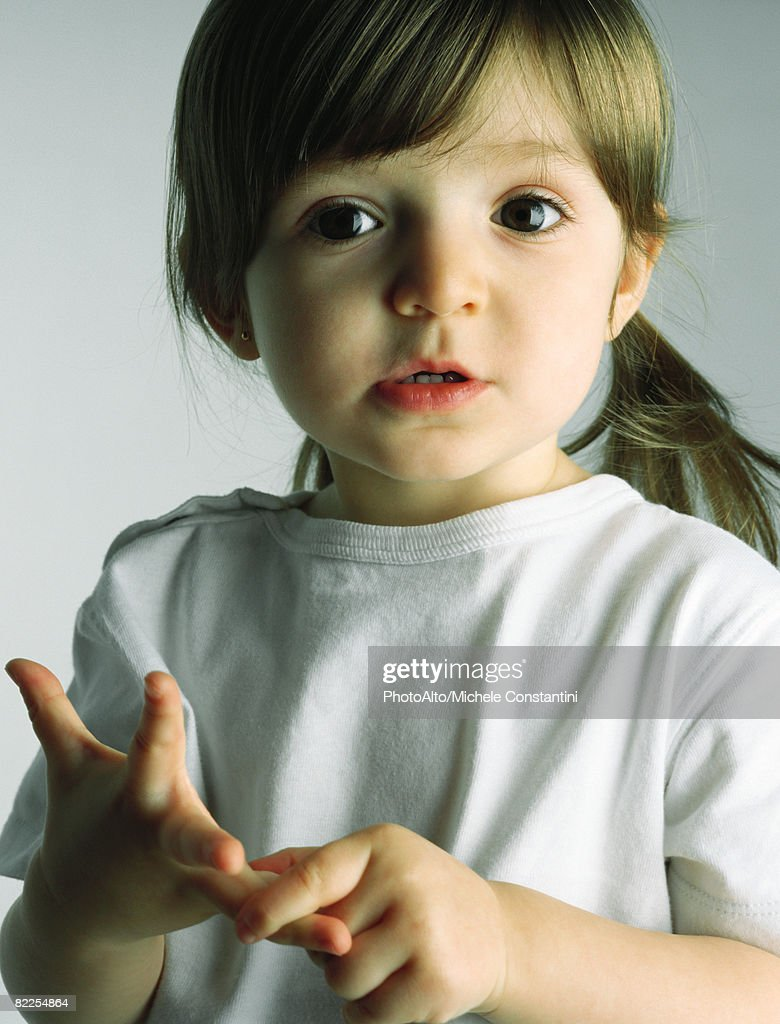 Little girl counting with her fingers, looking at camera, portrait : Stock Photo
