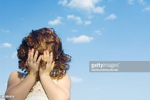 Little girl covering face with hair and hands outdoors, close-up