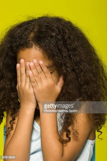 Little girl covering face with hands