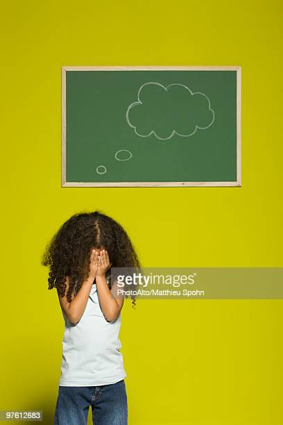 Little girl covering face with hands, thought bubble on chalkboard behind her