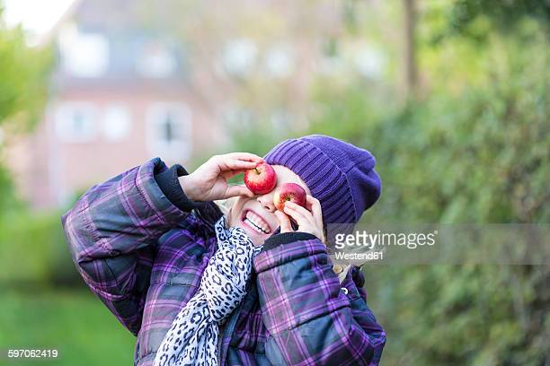 Little girl covering her eyes with two apples