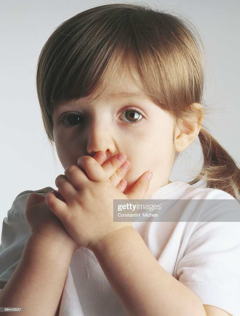 Little girl covering mouth, portrait : Stock Photo