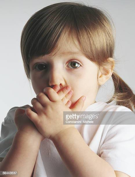 little girl covering mouth, portrait - girls open mouth stockfoto's en -beelden