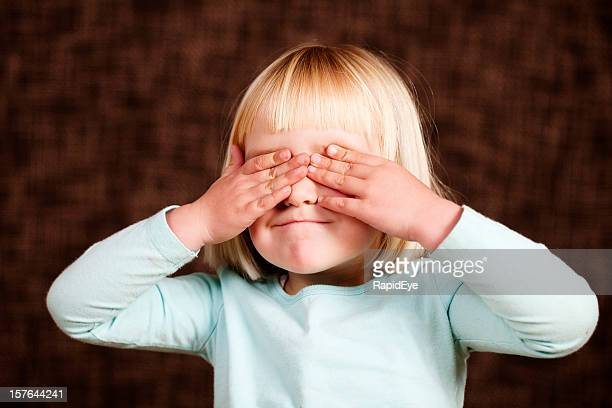 "Little girl covers her eyes to ""see no evil"""