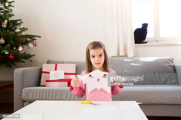 little girl crafting a Christmas Star