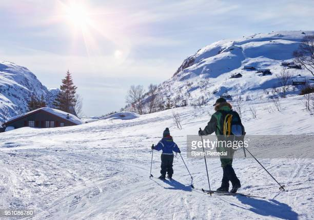 Little girl cross-country skiing with grandparent