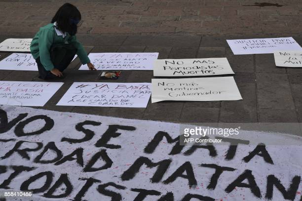 A little girl crouches amidst signs in front of the government's palace during a demonstration to demand justice for slain Mexican photojournalist...