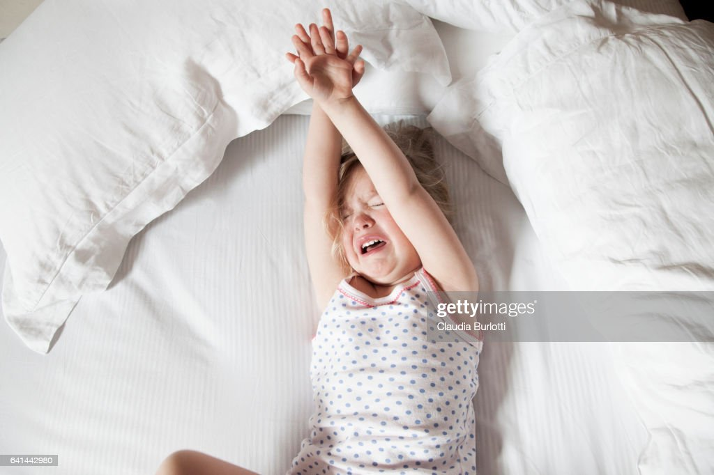 Little girl crying in bed : Stock Photo