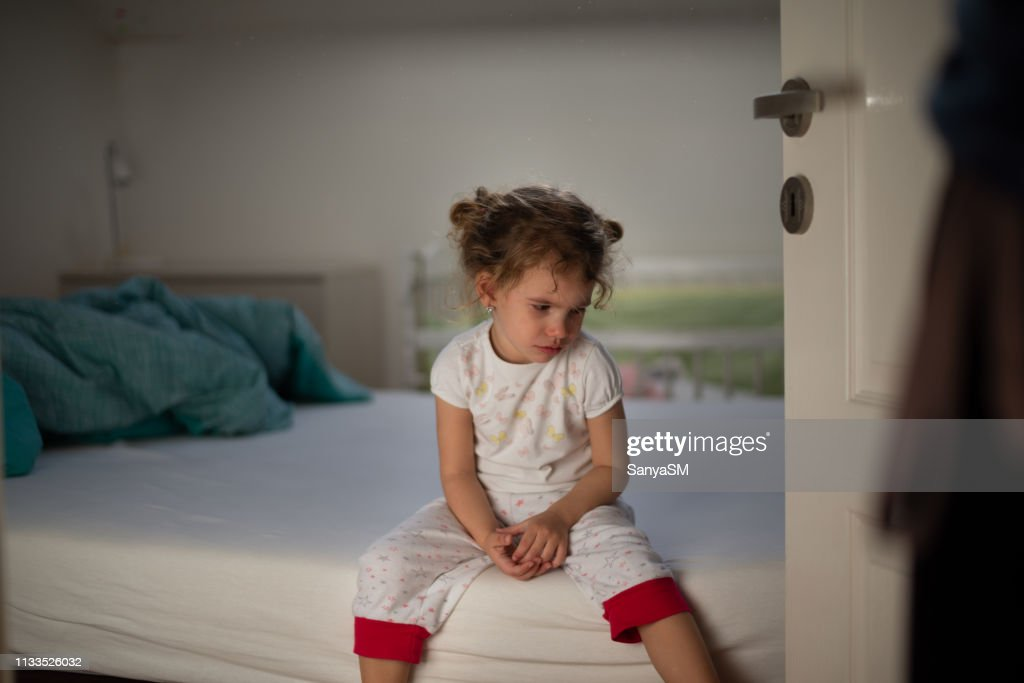 Little girl crying in bedroom : Stock Photo