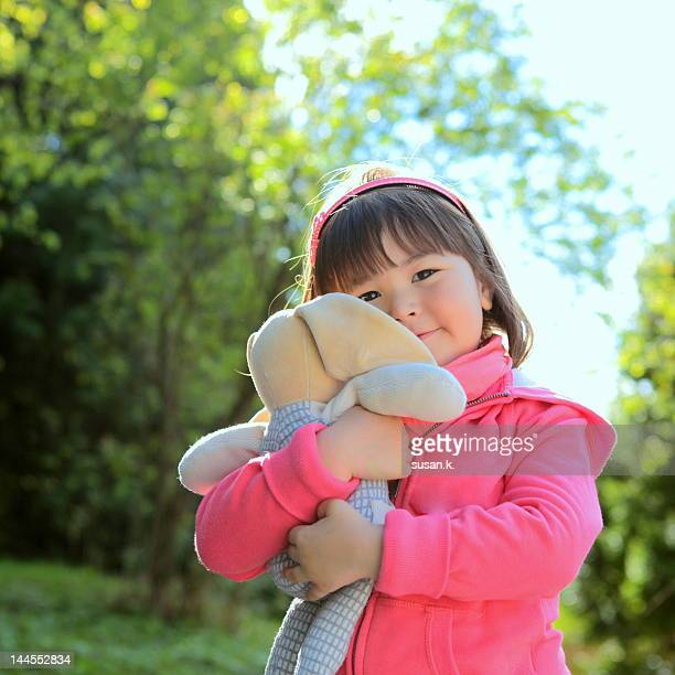 Little girl cuddling plush toy.