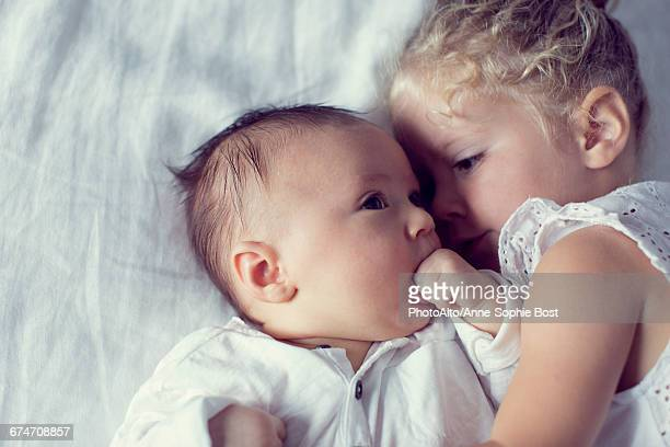 little girl cuddling with baby brother - 2 5 mesi foto e immagini stock
