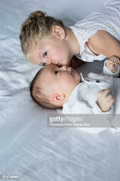 Little girl cuddling with baby brother