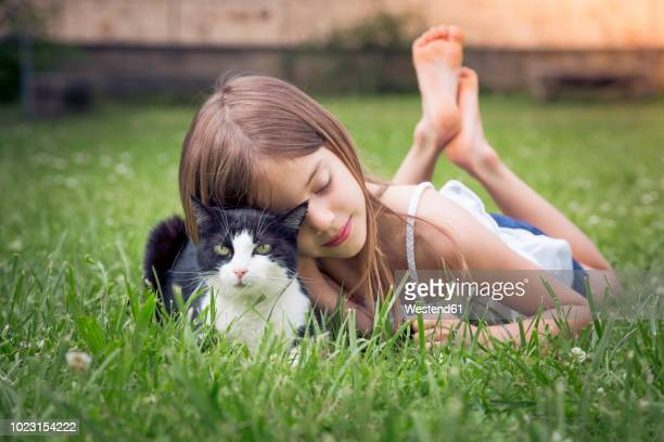 Little girl cuddling with cat on a meadow