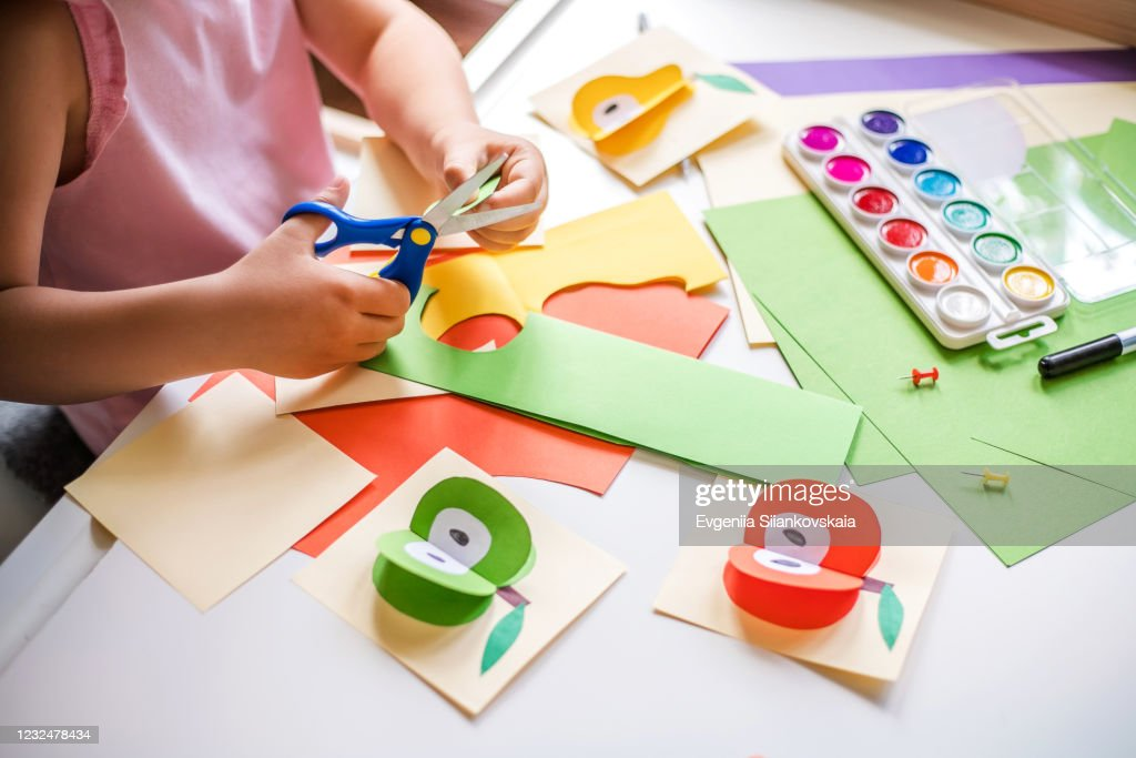 Little girl cutting colorful paper at the table. : Stock Photo