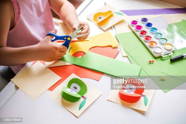 little girl cutting colorful paper at the table. - preschool child stock pictures, royalty-free photos & images