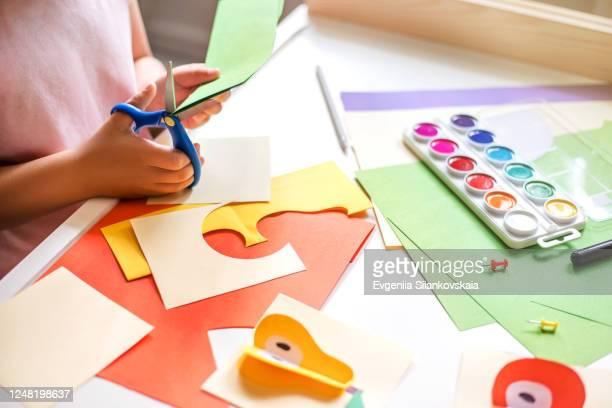 little girl cutting colorful paper at the table. - aplique arte de la costura fotografías e imágenes de stock