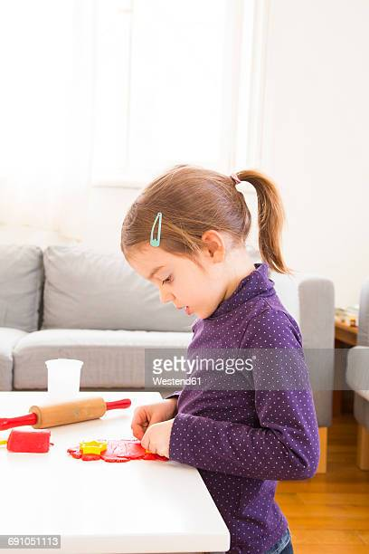Little girl cutting out modeling clay