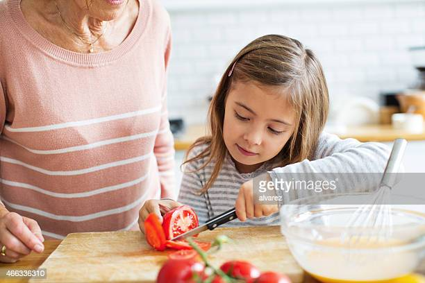 Little girl cutting tomatoes in the kitchen