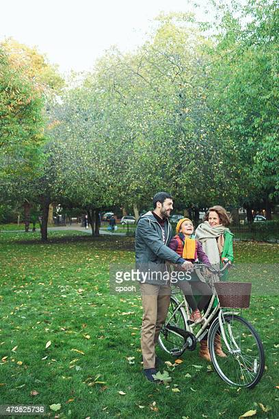 Little girl cycling with father and grandmother in park.