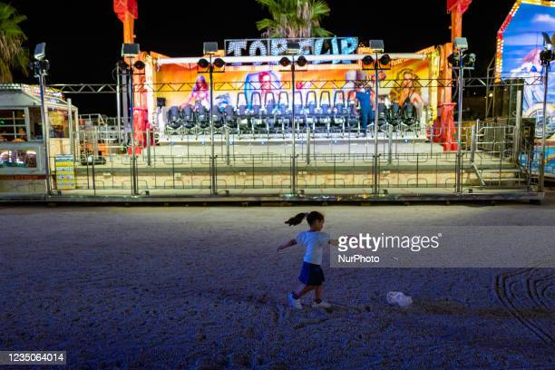 Little girl dances in front of an attraction on the first day of the Luna Park opening in Molfetta on 4 September 2021. On the occasion of the...