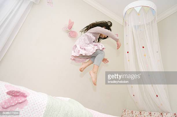 Little girl dancing and jumping on her bed