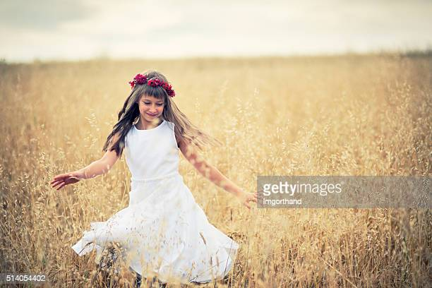 Little girl dancing in grain field