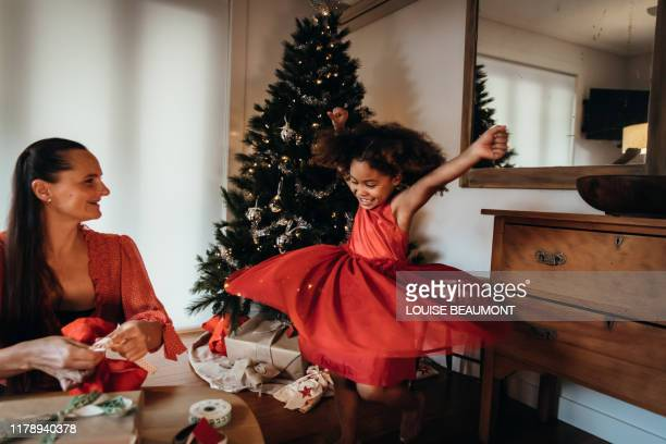 Little girl dancing in red Christmas Eve dress